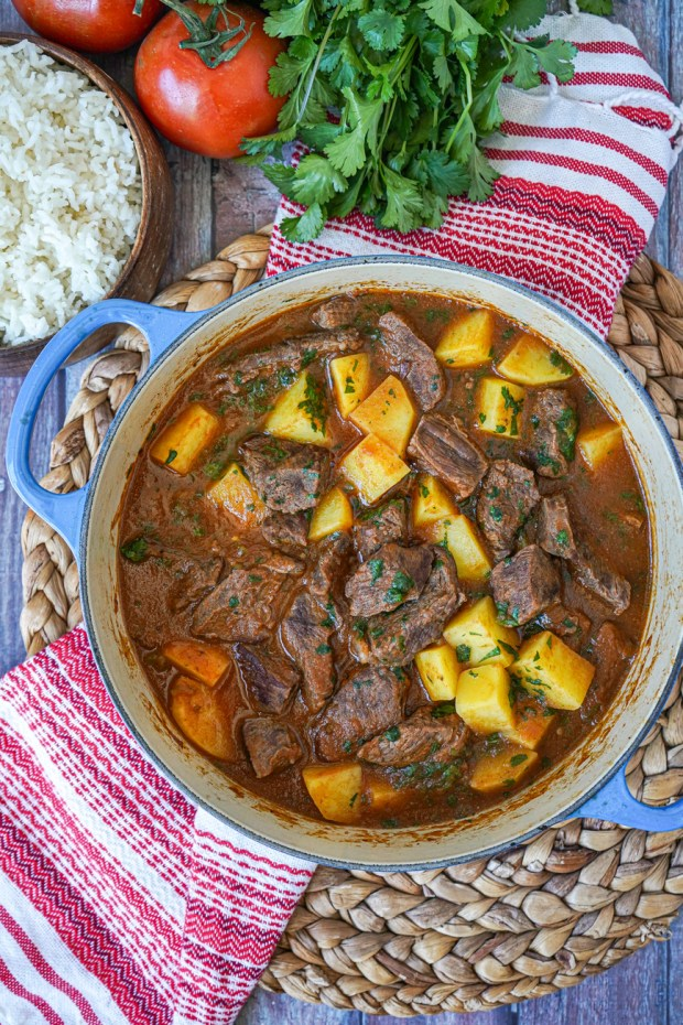 Aerial view of Carne con Papas (Beef and Potatoes) in a blue pot next to rice, tomatoes, and cilantro.
