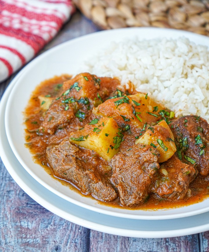 Carne con Papas (Beef and Potatoes) on a white plate with rice.