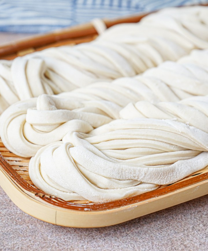 Three bundles of fresh Homemade Udon Noodles on a bamboo plate.