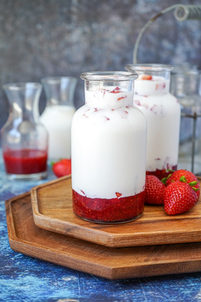 Side view of Korean Strawberry Milk in two glass jars on a wooden board.