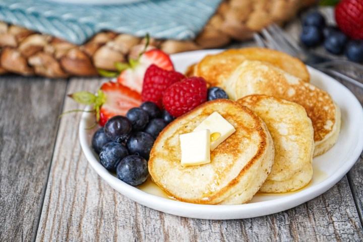 Four Silver Dollar Pancakes on a white plate with fresh berries, butter, and maple syrup.