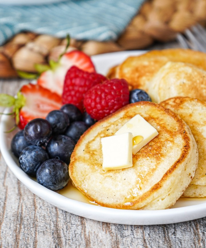 Four Silver Dollar Pancakes on a white plate with fresh berries.