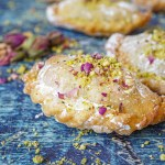 Close up of Almond Sanbuseh topped with powdered sugar, ground pistachios, and rose petals.