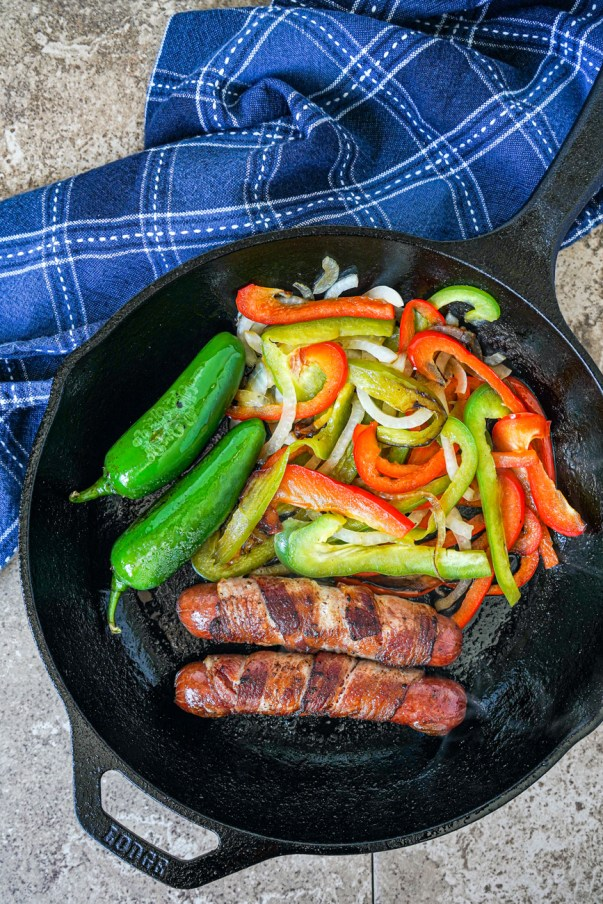 Bacon Wrapped Hot Dogs, jalapeño peppers, onions, and bell peppers in a cast iron skillet.