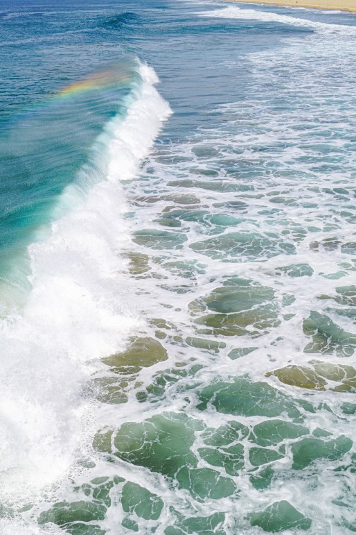 Wave with a reflection of a rainbow in ocean in Hermosa Beach.