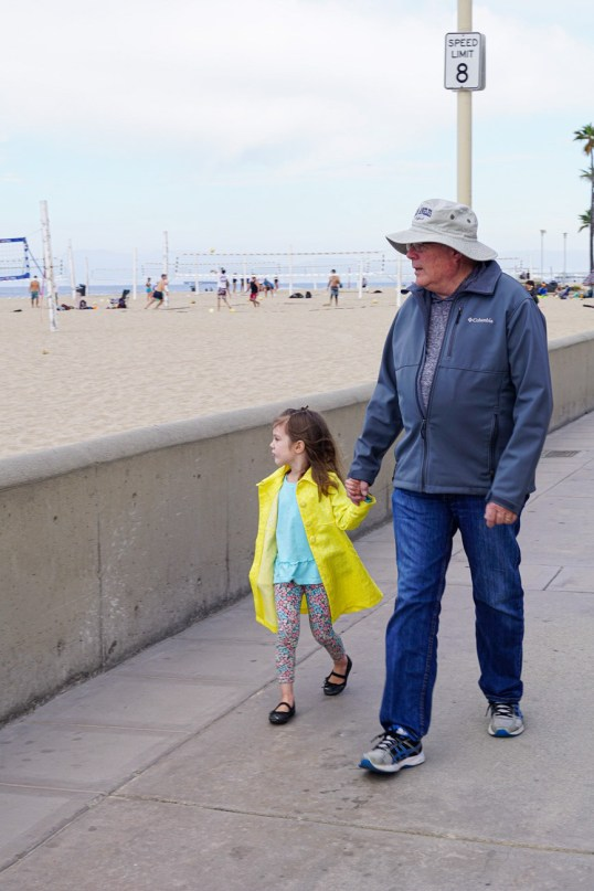 Girl and Grandfather walking down the Strand in Hermosa Beach next to the sand.