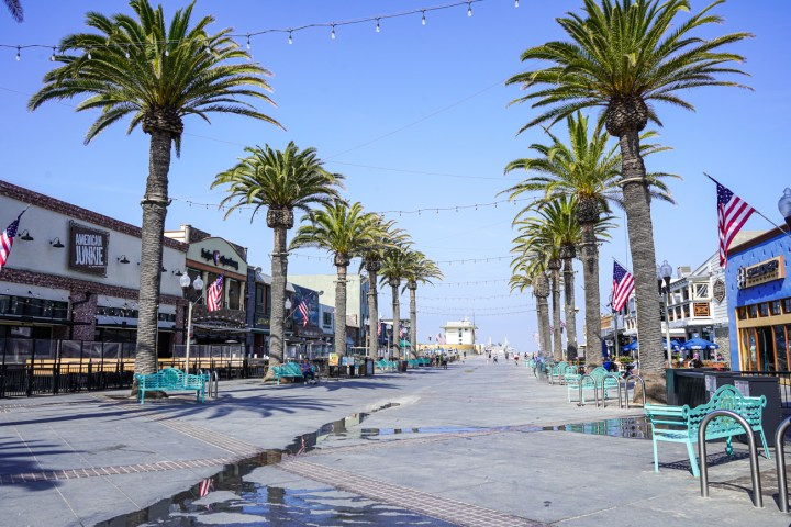 Pier Plaza in Hermosa Beach with shops, teal benches, and palm trees.