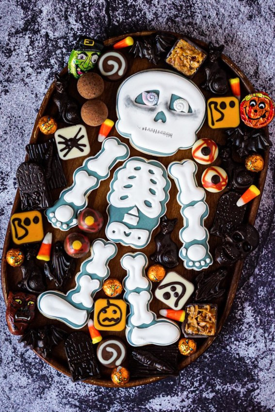 Skeleton Cookies from Sugar Dayne on wooden board with halloween chocolates.