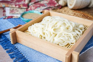 Cold Udon Noodles on a square plate with sesame miso sauce in background.