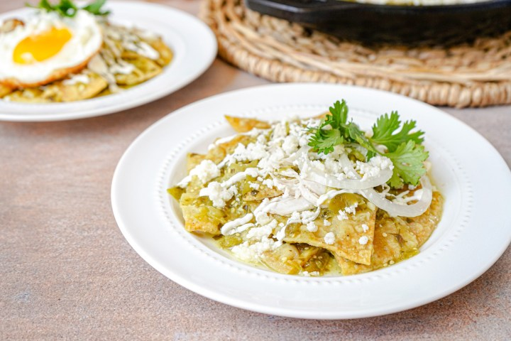 Chilaquiles Verdes on two white plates with fresh cilantro.