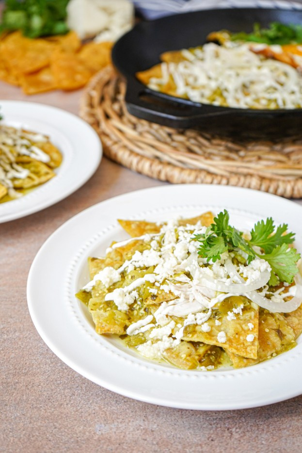 Chilaquiles Verdes on two white plates with a cast iron skillet in the background.