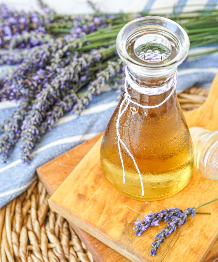 Homemade Lavender syrup in a jar on a wooden board next to fresh lavender.