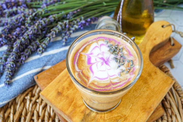 Latte with Homemade Lavender Syrup in a glass cup with purple and white swirls on top.