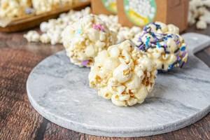 Three popcorn balls on a marble slab.