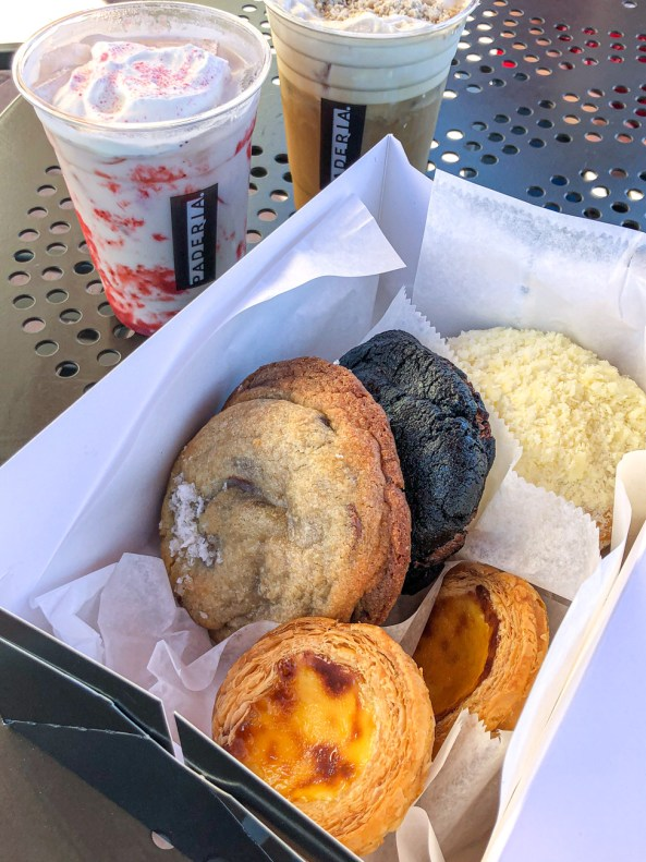 A box of cookies and tarts from Paderia Bakehouse next to two drinks.