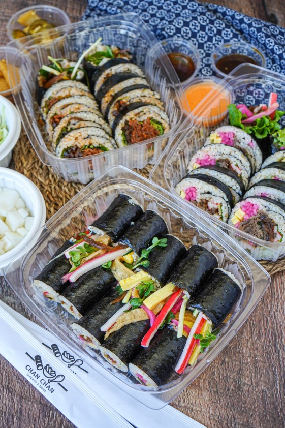 Kimbap in three plastic containers.