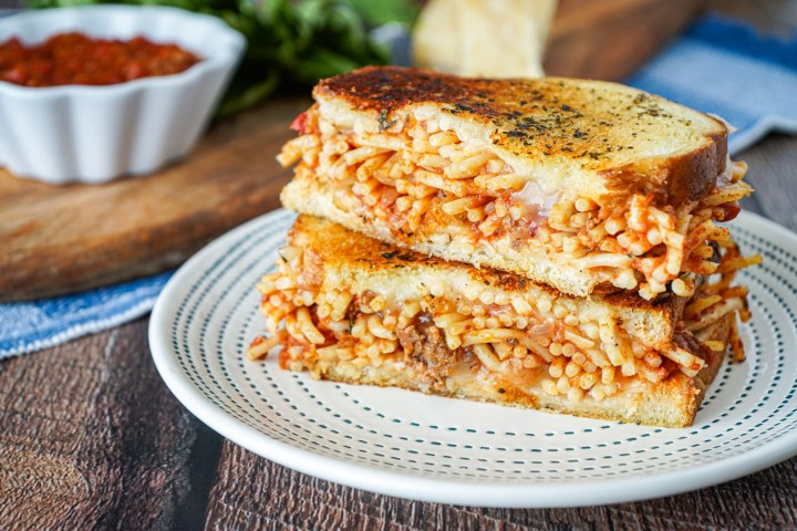 Two halves of a Spaghetti Grilled Cheese stacked on a plate.