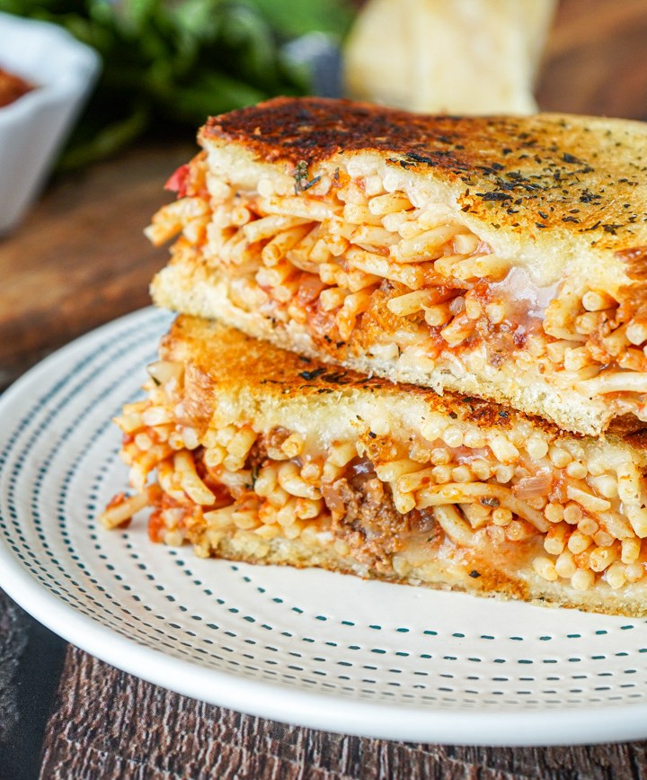 Two halves of Spaghetti Grilled Cheese stacked on a white plate with green lines.