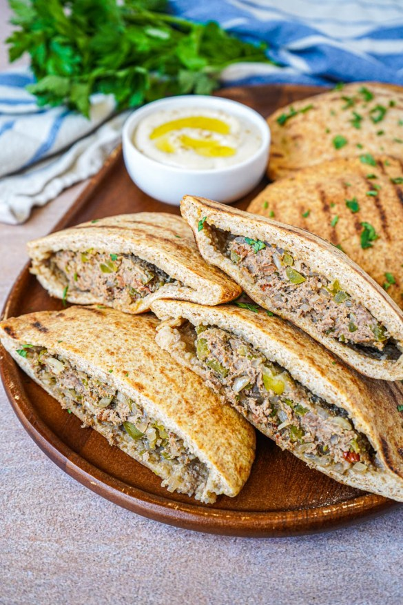 Close up view of Hawawshi (Egyptian Meat Stuffed Bread) cut into halves on a wooden board.