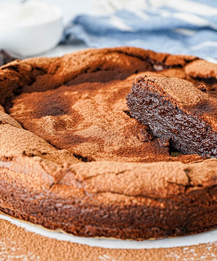 Flourless Chocolate Fudge Cake with a slice lifted up.