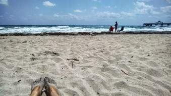 Laying on the beach, enjoying sunshine and warm water in Deerfield Beach, Florida.