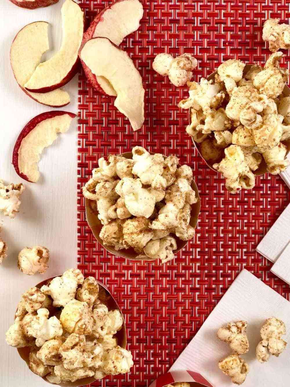 Apple cinnamon popcorn in red and white cups overhead