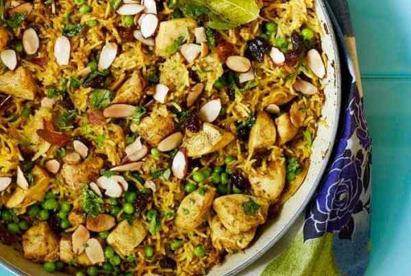 Chicken Biryani in a le creuset casserole on blue surface