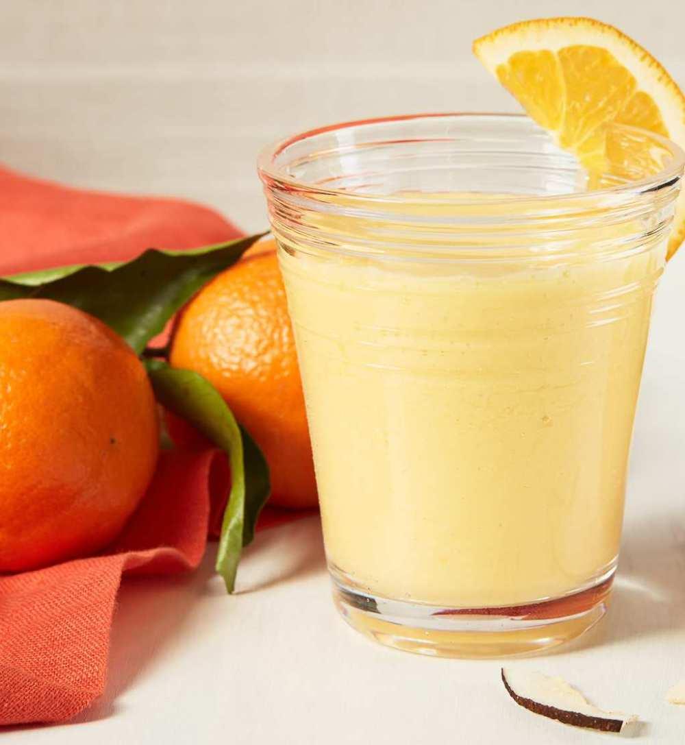 Mango smoothie with orange slice and whole oranges
