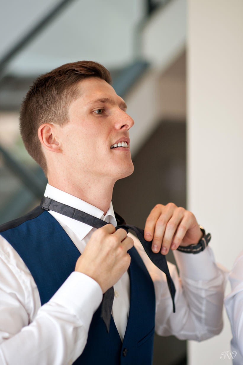 Groom ties his bowtie captured by Calgary wedding photographer Tara Whittaker
