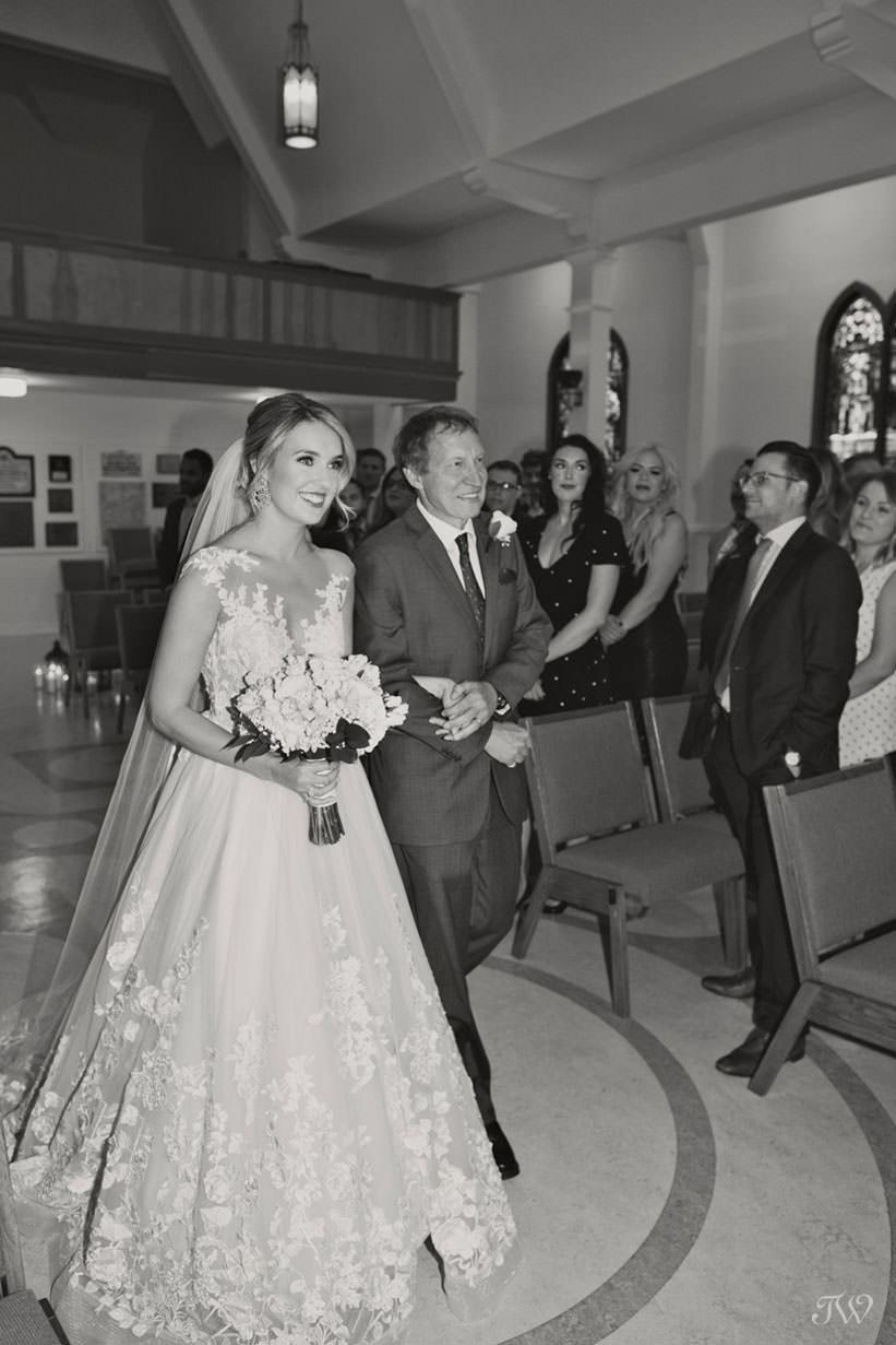 Bride walks down the aisle at St Stephen's Church captured by Calgary wedding photographer Tara Whittaker
