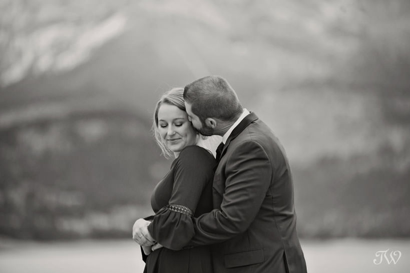 bride and groom embrace on the shore of Barrier Lake in Kananaskis captured by Tara Whittaker Photography
