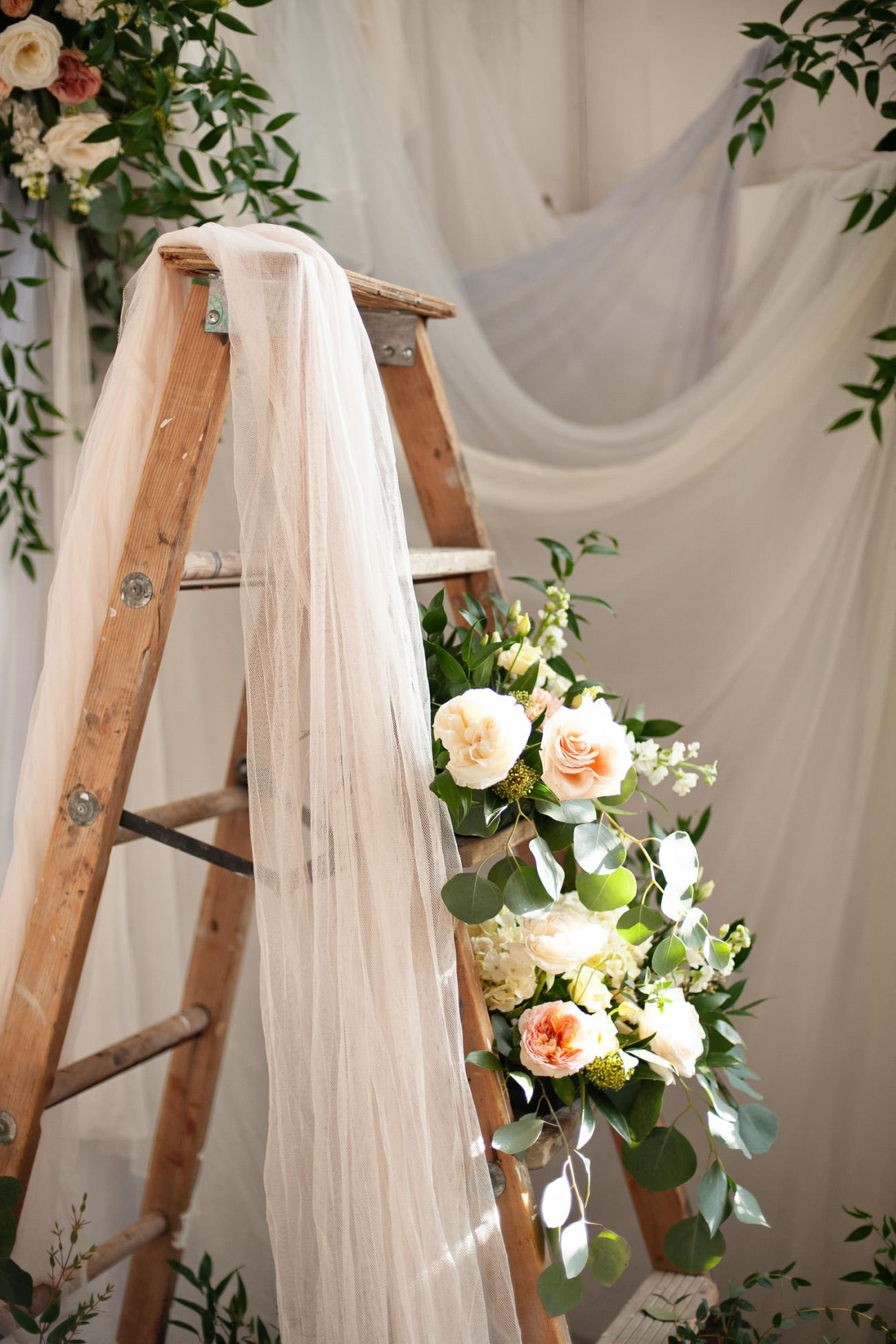 vintage ladder draped with textiles captured by Tara Whittaker Photography