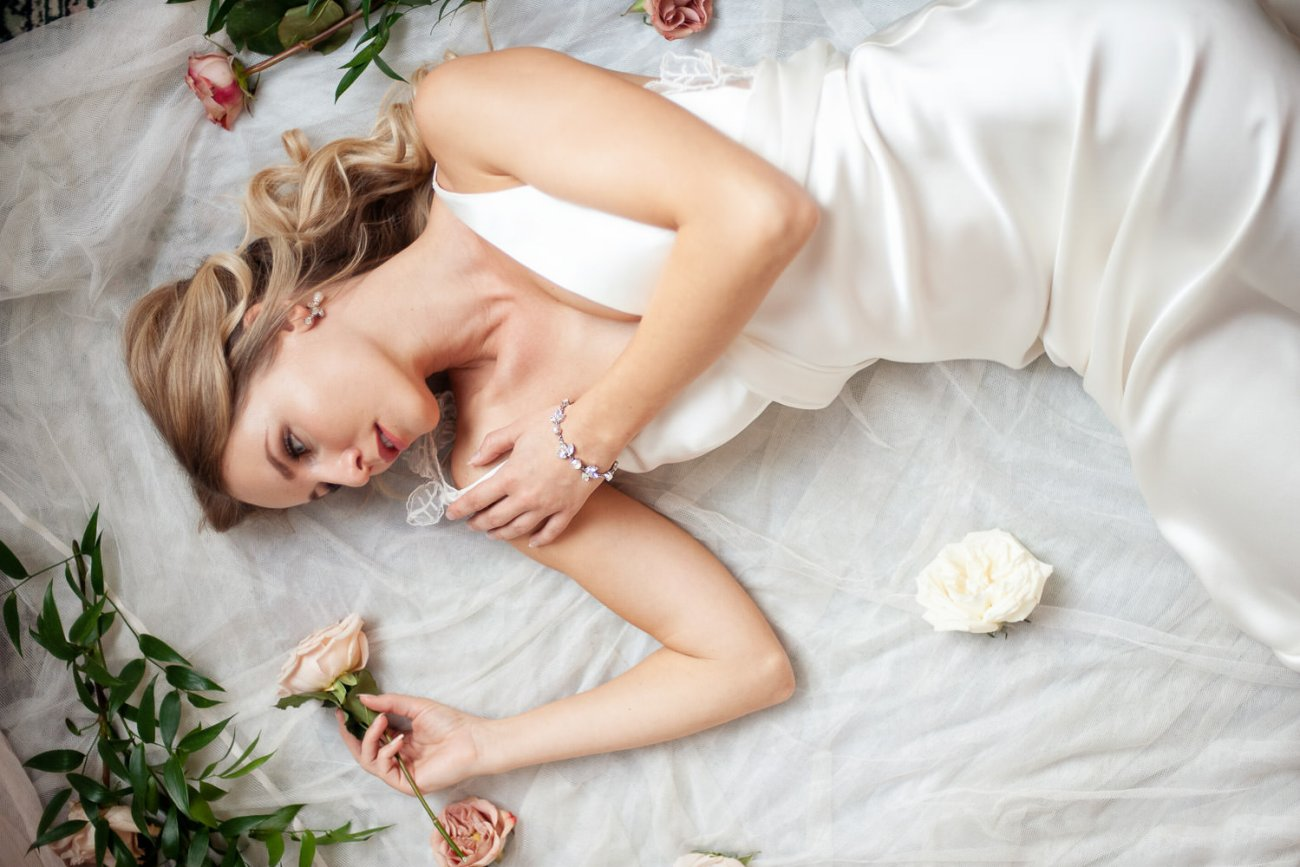bride lying with flowers and greenery around her captured by Tara Whittaker Photography