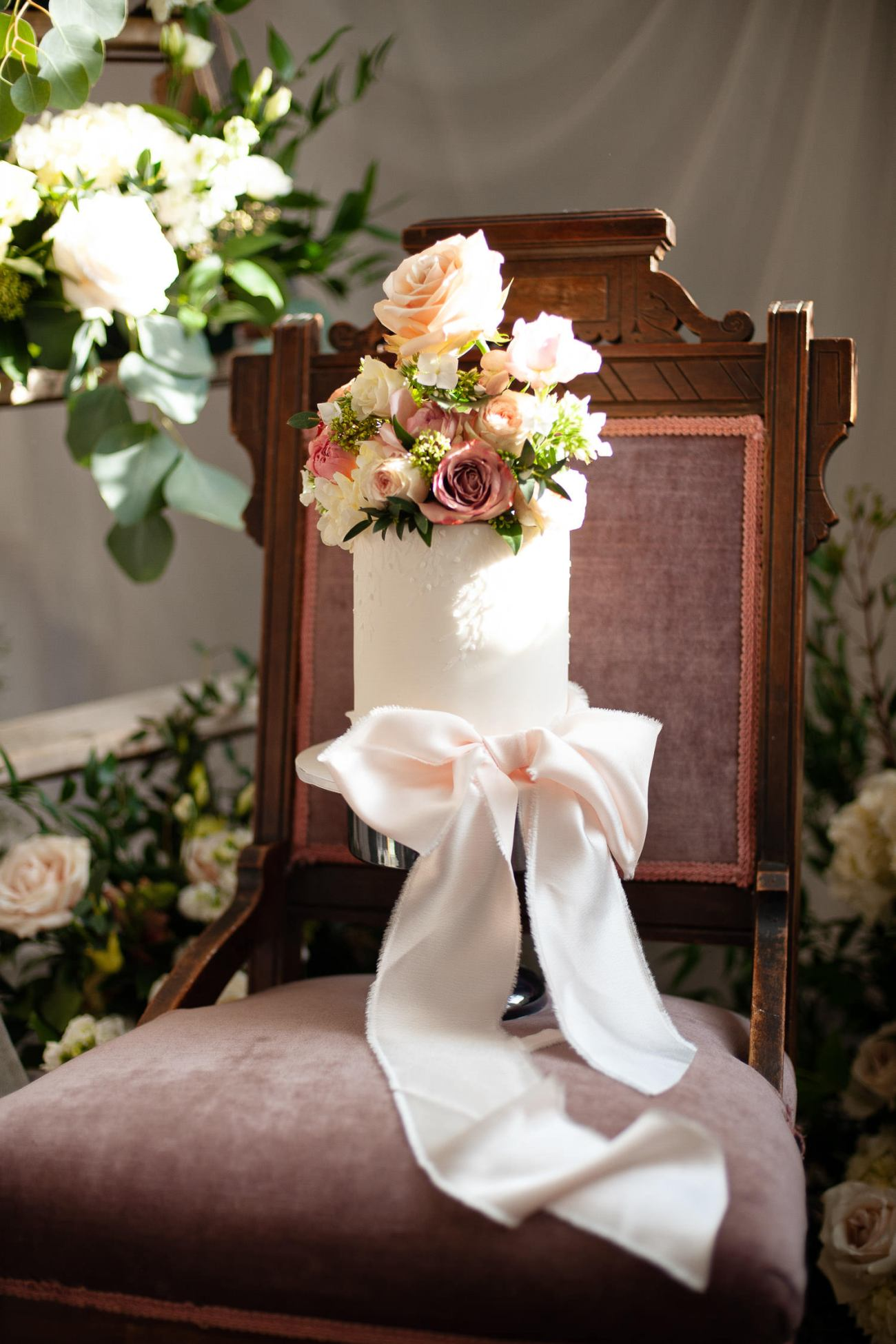 wedding cake with flowers and a large pink bow captured by Tara Whittaker Photography