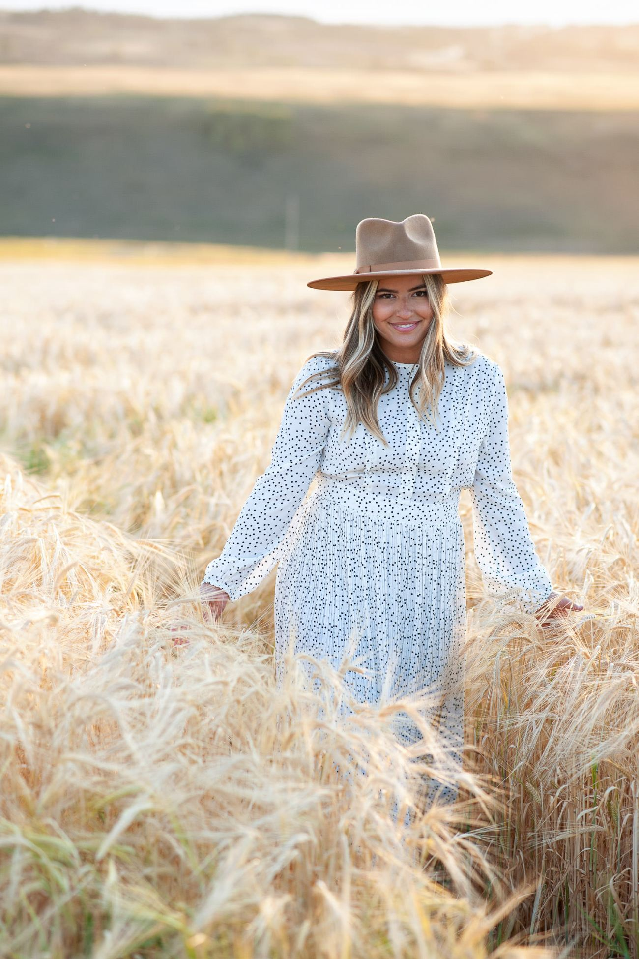bride wears a pleated dress and wool hat during engagement session with Tara Whittaker Photography