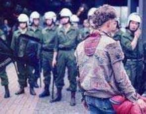 Un punk frente a un grupo de policías