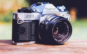 """An old Canon camera, reads """"Canon - Lens made in Japan."""""""