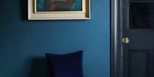 A bright orange ottoman in front of a dark blue wall with a painting of a woman.