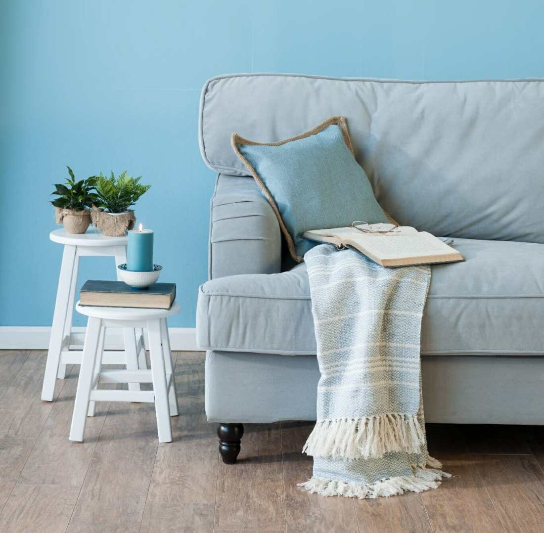 A gray couch in front of a light blue wall. Tar Heel Painters in Chapel Hill, NC.