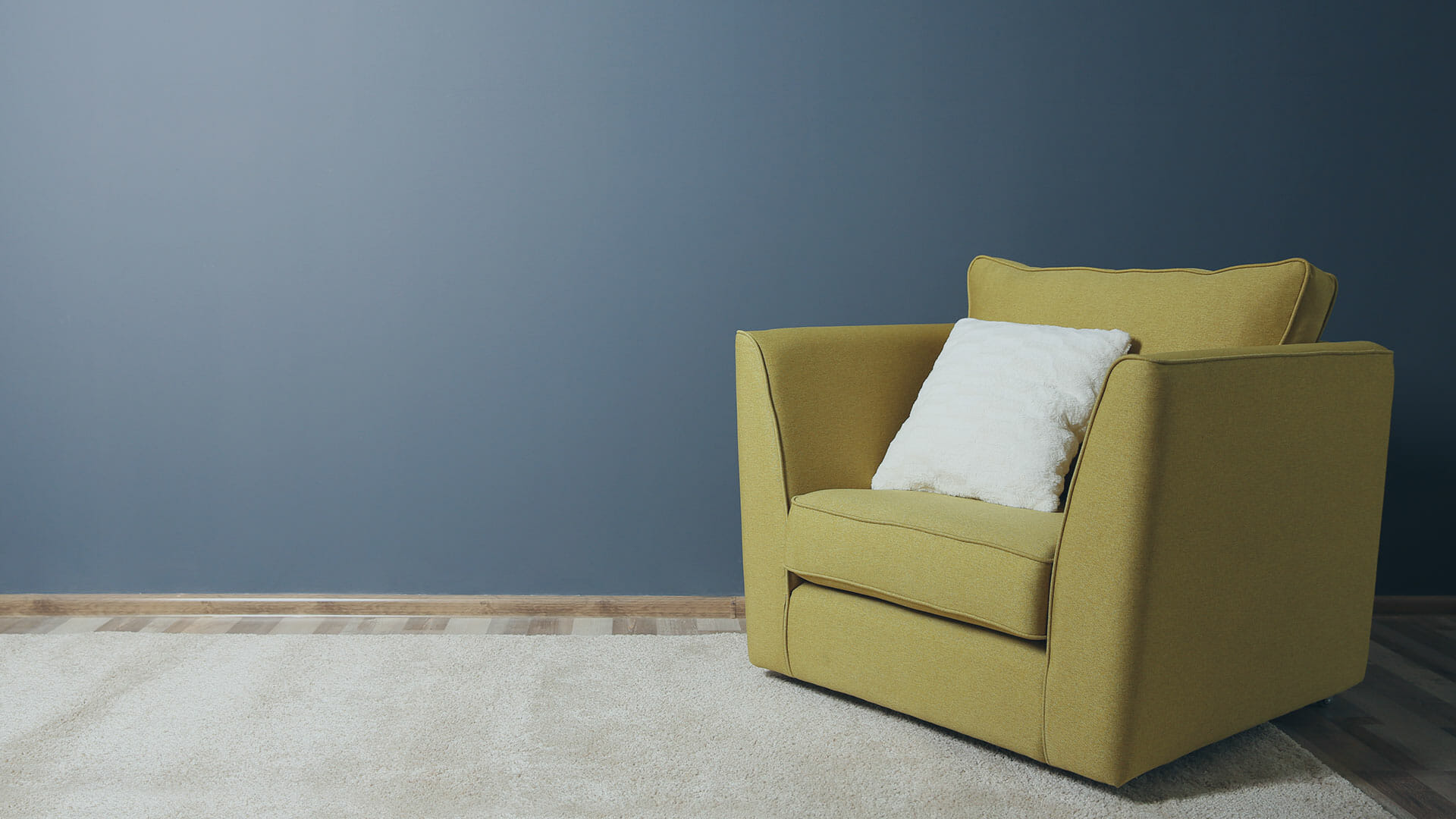 A yellow armchair in front of a dark blue wall.