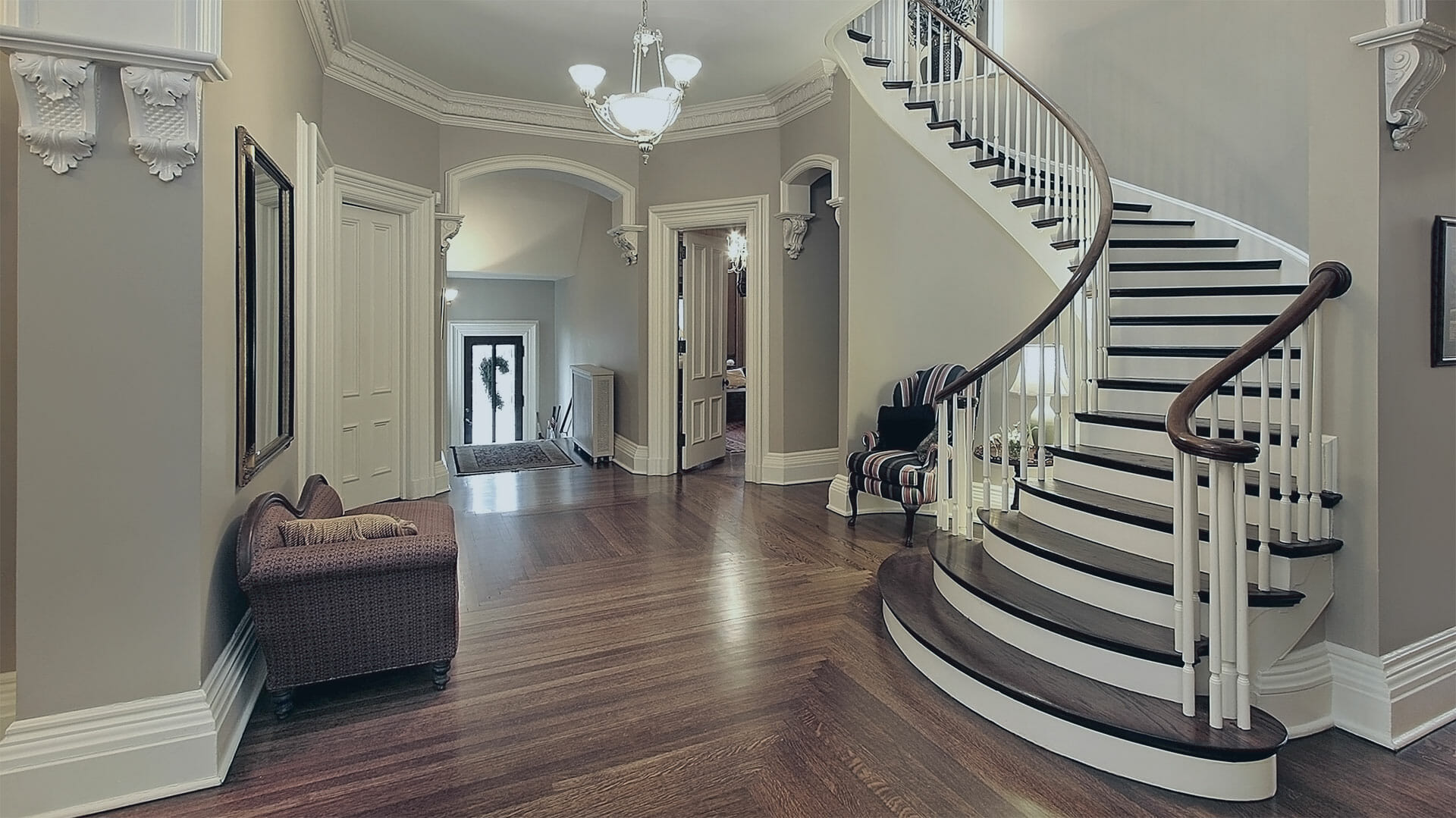 Grand staircase opening into a foyer with wood floors, taupe walls and white crown molding.