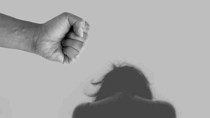 hand waving fist at a woman, where the perpetrator is committing domestic violence against their partner