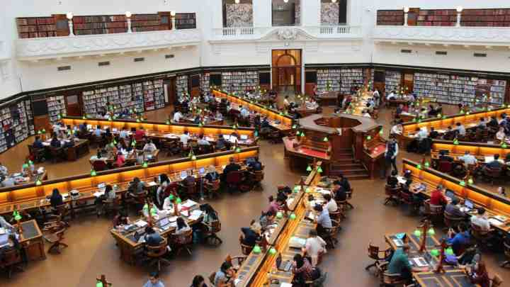 a busy college or university library with students studying at desks.