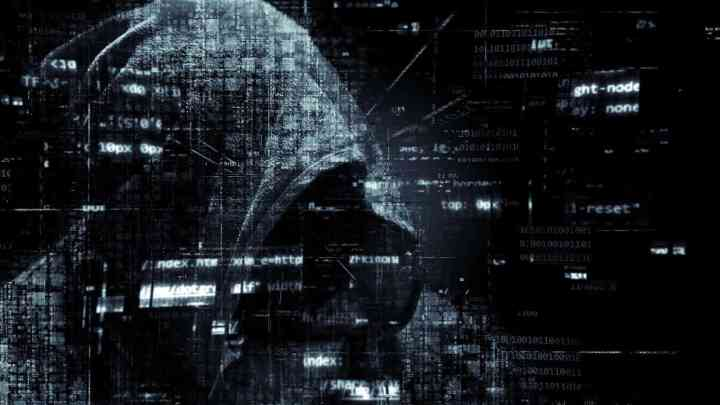 a hooded person with an overlay of code segments, to signify a person computer hacking