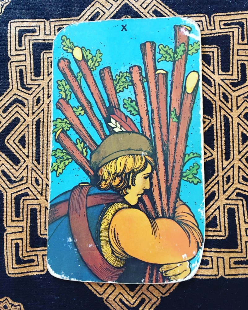 Ten of Rods Tarot card. a man holds ten rods and has to carry them. The card is about carrying a burden and having courage to be strong in tough times.