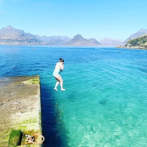 Girl jumping in at Elgol Pier