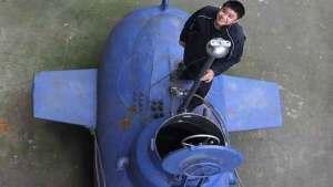 المخترع الصيني تشانغ وُيي إلى جانب غواصته الجديدة