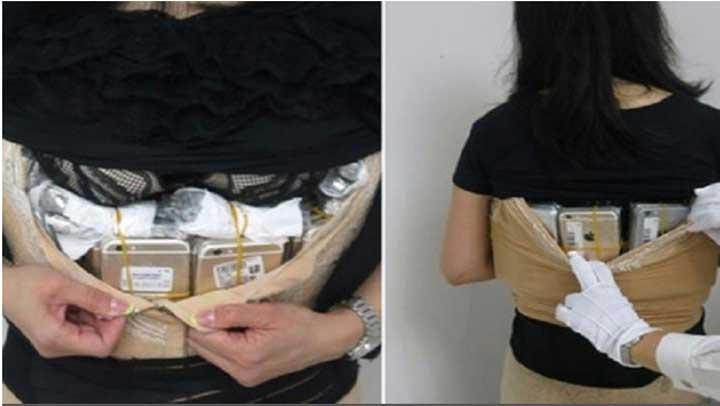 صينية تحاول تهريب 100 آيفون تحت ملابسها