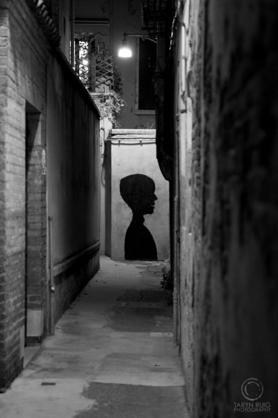 Alleyway in venice with a silhouette face painted on a wall