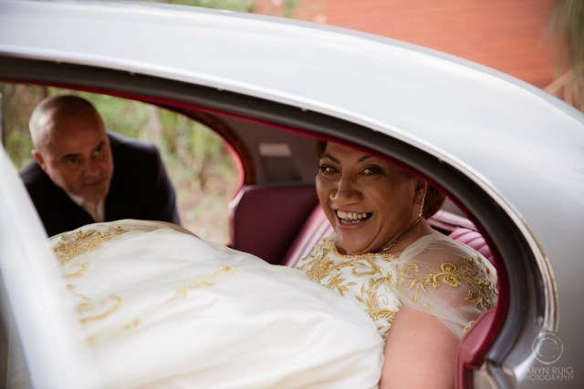 bride in wedding car laughing